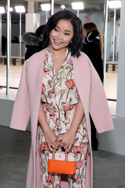 Lana Condor attended the Tory Burch Fall 2019 show carrying an orange and pink leather purse from the brand.
