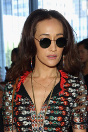 Maggie Q hid her eyes behind a pair of Ray-Ban shades while posing for photographers at the Tory Burch fashion show.