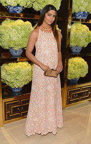 Camila Alves accessorized her outfit with an elegant gold Tory Burch box clutch.