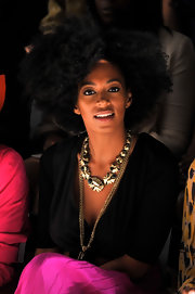 Solange Knowles rocked NYFW in a statement gold necklace paired with a fuchsia maxi skirt.