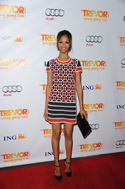 Zoe Saldana kept all eyes on her retro print mini dress by teaming it with a sleek black envelope clutch.