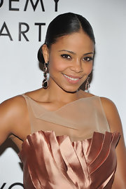 Sanaa Lathan pulled her hair back in a center part bun that she paired with elegant gemstone earrings.