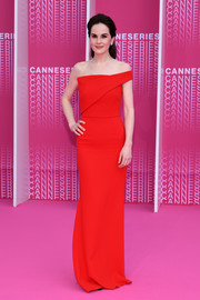 Michelle Dockery looked supremely elegant in a red off-one-shoulder column dress by Roland Mouret at the Cannes International Series Festival screening of 'The Truth About the Harry Quebert Affair.'