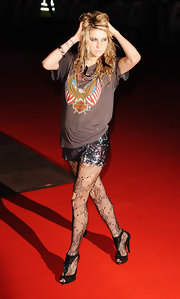 Kesha wears a worn in Harley tee with sequined shorts and torn fishnet tights.