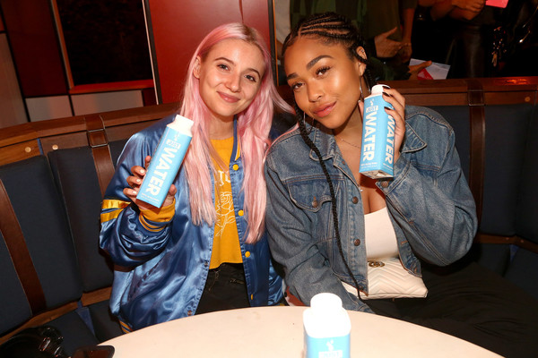 Jordyn Woods toned down her sexy low-cut top with a denim jacket for the Umami Burger x Jaden Smith Artist Series launch.