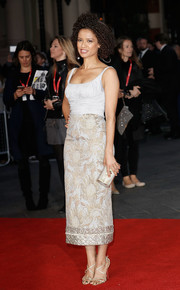 A gold tube clutch polished off Gugu Mbatha-Raw's ensemble.