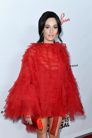 Kacey Musgraves matched a red hard-case clutch by Edie Parker with a tiered mini dress for the Universal Music Group's 2019 Grammy afterparty.