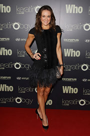Michelle Bridges added sophistication to her feathered frock with a black and pewter metallic clutch.