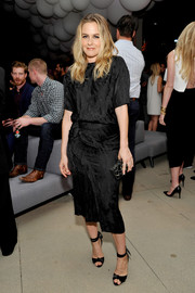 Black ankle-strap sandals with knot detail completed Alicia Silverstone's outfit.