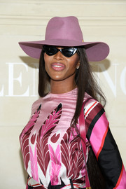 Naomi Campbell topped off her look with a purple sun hat.