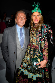 Anna dello Russo was elaborately styled at the Valentino fashion show with this fringed green crocodile clutch, cape, and dress combo, all by Valentino.