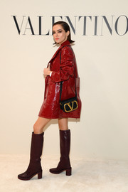 Zoey Deutch teamed a black Valentino shoulder bag with a patent coat and knee-high boots for the brand's Fall 2020 show.