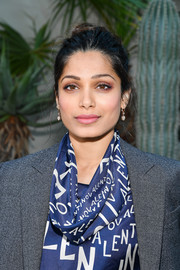 Freida Pinto wore her hair in a casual bun at the Valentino Spring 2019 show.