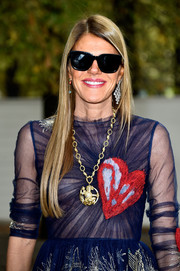 Anna dello Russo wore a huge gold pendant necklace with a heart-embellished dress at the Valentino fashion show.