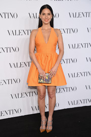 Olivia Munn cut a youthful and flirty figure in an orange fit-and-flare mini dress by Valentino during the brand's Sala Bianca 945 event.