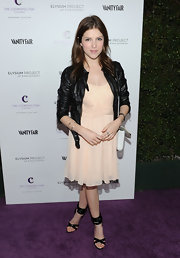 Anna dons a black leather jacket over a cream chiffon dress for a tough-chic ensemble.