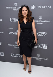 Salma Hayek completed her all-black look with a large suede clutch.