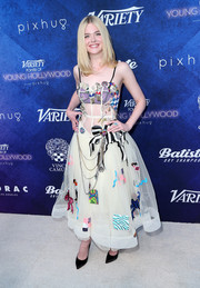 Elle Fanning opted for minimal styling with a pair of black satin pumps.