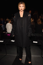 Kylie Jenner covered up her curves in a black Vera Wang cutout-shoulder coat when she attended the brand's fashion show.