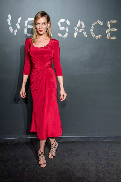Uma Thurman styled her dress with strappy black sandals by Jimmy Choo.