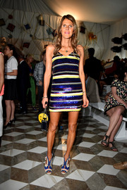 Anna dello Russo hit the Versace fashion show looking party-ready in a sequined, striped mini dress by Ashish.