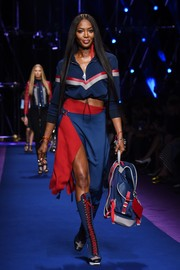 Naomi Campbell showed some leg in a blue and red wraparound skirt.
