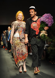 Vivienne Westwood took a bow during her Spring 2012 menswear fashion show wearing a cutout dress with a vibrant print.