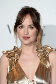 Dakota Johnson attended the Vogue 100: A Century of Style event wearing her usual messy ponytail.