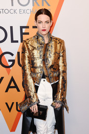 Riley Keough accessorized with a black Louis Vuitton box clutch at the 'Volez, Voguez, Voyagez' exhibition opening.