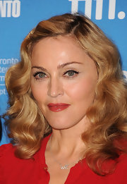 Madonna's wore her hair in wavy locks at the 'W.E' press conference in Toronto. To try her look, set hair in hot rollers vertically and brush curls out to smooth and soften.