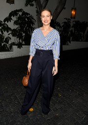 The actress finished her Sailor-inspired outfit with a crimson lip and brown bowler purse and high-waisted pants.