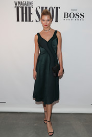 Karlie Kloss paired her lovely dress with a black satin clutch.