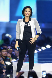 Demi Lovato spoke on stage during WE Day California wearing a tricolor bomber jacket and skinny jeans.