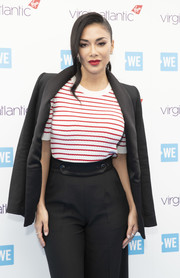 Nicole Scherzinger arrived for WE Day UK 2019 wearing a black blazer over a striped knit top.