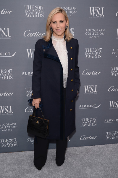 Tory Burch styled her outfit with an elegant black crocodile tote.