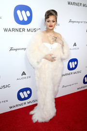 Andra Day made a glam appearance at the Warner Music Group Grammy celebration in a floor-length cream-colored fur coat.