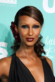 Iman looked ultra sophisticated as always in a deep side parted curled ponytail. She accented her look with a burgundy flower.