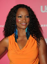 Garcelle Beavais added a vibrant pop of color to her look with bold blue feathered earrings.