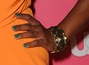 Garcelle Beauvais added a contrasting color to her orange frock with emerald green tips.