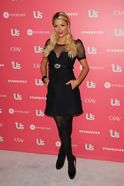Paris Hilton teamed her ladylike black cocktail dress with matching patent platform pumps.