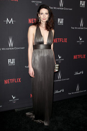 Caitriona Balfe flashed her cleavage in a metallic halter gown at the Weinstein Company Golden Globes party.