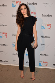 Emmy Rossum teamed her outfit with a chic gray hard-case clutch.