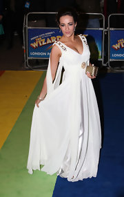 Stephanie looks great in this white gown with cutout shoulders and gold skull embellishments.
