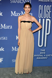Tao Okamoto wore a light tan strapless gown with a black bow accent at the bust.