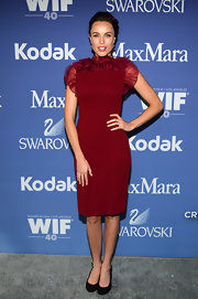 Jessica McNamee looked sleek and sophisticated in a ruby red cocktail dress with a ruffled neckline.