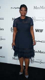 Octavia Spencer showed her classic elegant style in a navy jersey dress with a lace neckline and paneling.