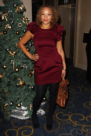 Angela Griffin paired a ruffled burgundy dress with a cognac colored leather satchel. The bag's decidedly casual vibe contrasted with her festive attire.