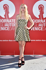 Dakota Fanning chose a strapless fit-and-flare mini dress by Miu Miu for the 'Women's Tales' photocall at the Venice Film Festival.