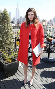Lake Bell complemented her coat with an oversized white clutch.