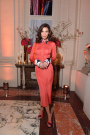 Bella Hadid showed off her slim physique in a clingy coral shirtdress by Emilio Pucci at the YouTube cocktail party during Paris Fashion Week.